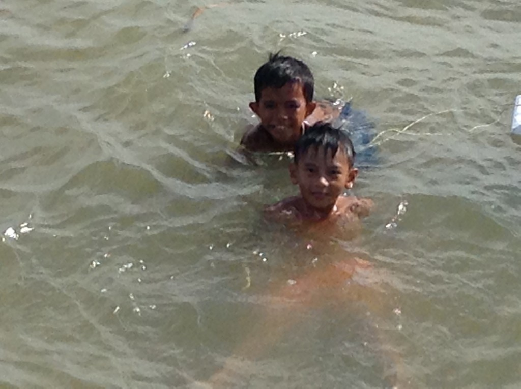 Little boys swimming at the fish dock having a blast!