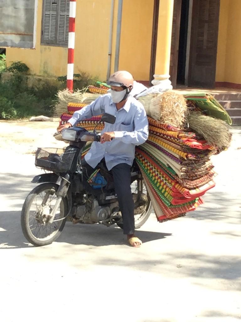 Taking hand mats grass mats to market.