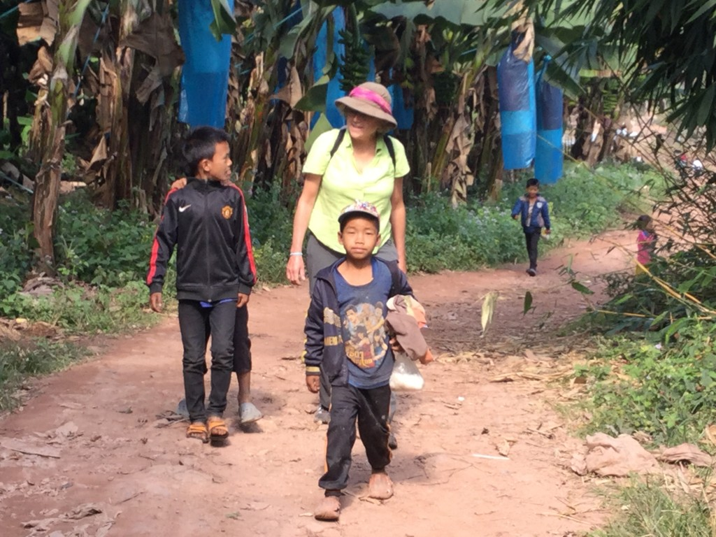 Denise walking down the tail surrounded by village children. We have similar pictures from Nepal, taken 25 years ago.