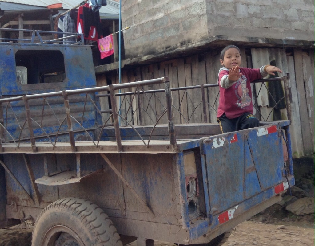 A little boy plays on the back of a truck.