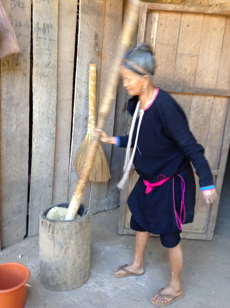 A lady making rice flour the hard way. People are very strong in these villages.