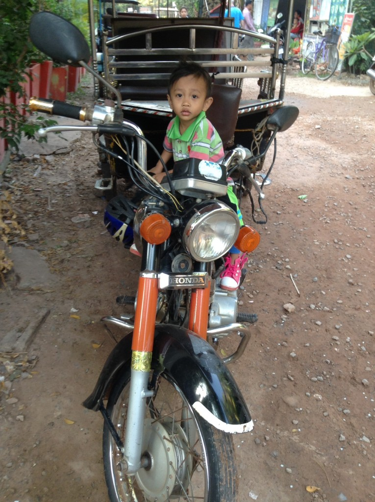 This little guy was sitting in his dad's seat on the motorcycle that pulled the tuk-tuk.