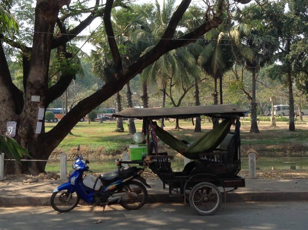 A tuk-tuk driver taking a nap in the middle of the day which is very common in all of southeast Asia.