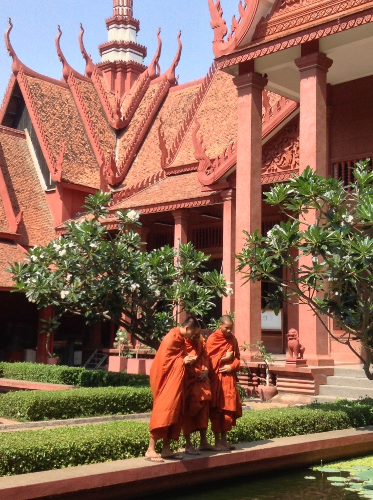 Monks who seem to be engaged at looking at their devices at the Royal Palace grounds.